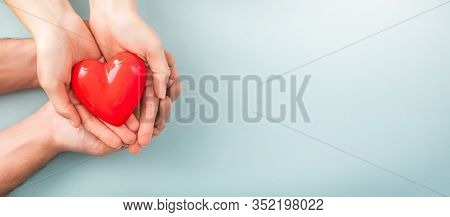 An Adult, Mother And Child Hold A Red Heart In Their Hands. Concept For Charity, Health Insurance, L