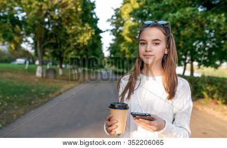 Beautiful Girl Teenager Schoolgirl, Summer Park, Hand Smartphone, Cup With Tea And Coffee. Casual Wa
