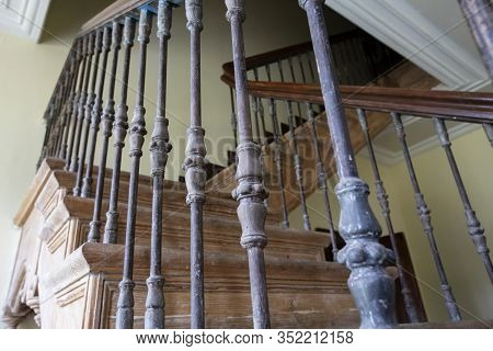 Ancient Staircase With Iron Balusters And Wooden Railing.
