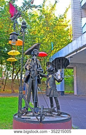 Kiev, Ukraine - Aug 30, 2019: Forged Metal Girl With Umbrella And Men Statue In The Kyiv City Psychi