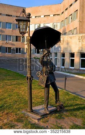 Kiev, Ukraine - Aug 30, 2019: Forged Curly Metal Men Statue With Umbrella In The Kyiv City Psychiatr