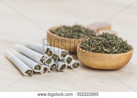 Joint Of Marijuana. Spoon Filled With Weed, Grinder And Wooden Background. Rolling A Joint And Smoki