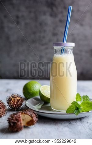 Tropical Drink Pineapple And Rambutan Smoothie With Coconut Milk In A Glass Bottle
