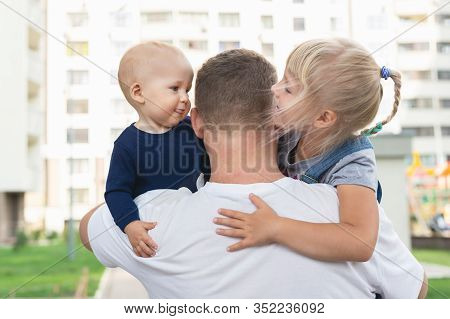 Back View Of Father Holding Two Adorable Sweet Cute Siblings On Hands During Walk Outdoors. Little S