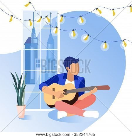 Young Guy Sitting On Floor Playing Guitar On Background Big Window. Coworking Center. Hobby Young Pe
