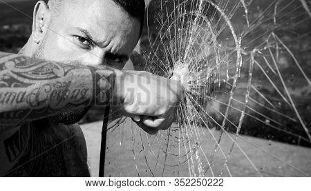 Destroy Obstacles. Man Muscular Body Punching. Handsome Brutal Man Near Broken Glass. Brutal Handsom
