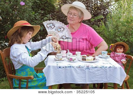 Grandmother And Granddaughter Enjoying A Formal Garden Tea Party