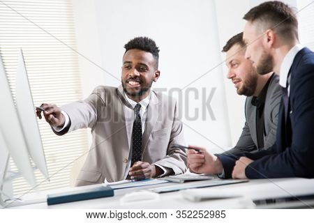 Multy-ethnic group of young business people sitting at the office desk and working with computer