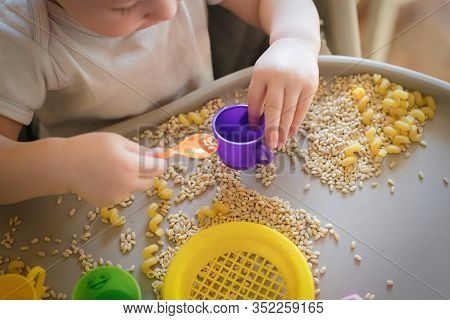Small Kid Pours Toy Yellow Spoon Ful In Cup. Games With Products. Montessori Technique. Development