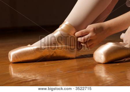 Ballerina Adjusting En Pointe Ballet Shoes (Slippers)