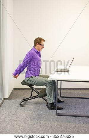 male office worker sitting on kneeling stool, stretching arms during short break in work at his desk in the office