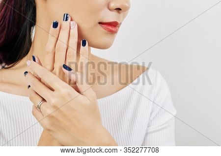 Young Beautiful Woman Touching Her Face With Well-groomed Hands With Blue Nail Polish