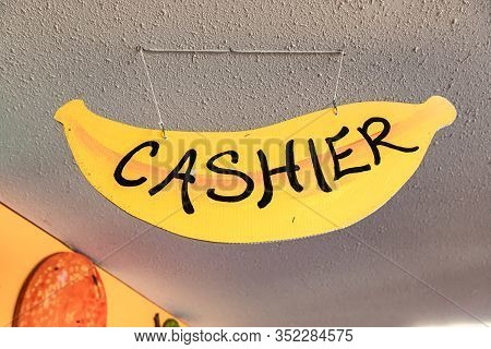 Hand Written Banana Shaped Signboard At The Local Food Market. Sign Reads Cashier In Big Black Capit