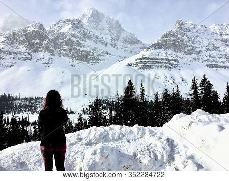 A Young Woman Admiring An Incredible View Of A Dark Green Forest In The Foreground And Snow Covered
