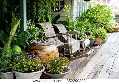 Wooden Rocking Chairs In A Cottage Garden Porch Setting On Wooden Floor In Vintage Thai Botanical Ga