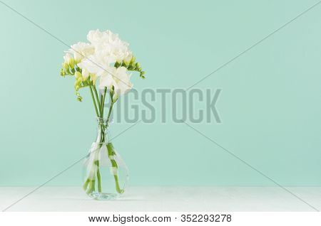 Fresh White Freesia Flowers In Elegant Transparent Vase On Soft Light Green Mint Menthe Wall And Whi