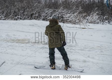 Active Man Snowboarder Riding On Slope. Man Snowboarder Snowboarding On White Snow. Back View Of Mal