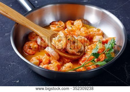 Seafood Dish Shrimp Scampi With Garlic Butter Sauce With Parsley, On A Skillet On Concrete Backgroun