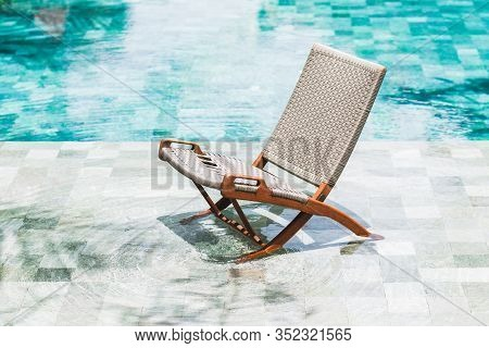 Folding Rattan Chair Chaise Longue By The Pool. Clear Transparent Water In Pool