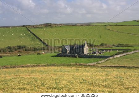 The tiny St Rhwydrus Church nestled agmonst the fields of Hen Both Bay poster