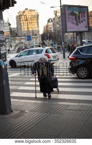 Belgrade, Serbia - 22.2.2020. Old Woman Walking. Pensioner Lifestyle. Old Woman Crossing Street. Urb