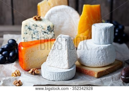 Cheese Assortment: Blue Cheese, Hard Cheese, Soft Cheese On A Parchment Paper. Wooden Background. Cl