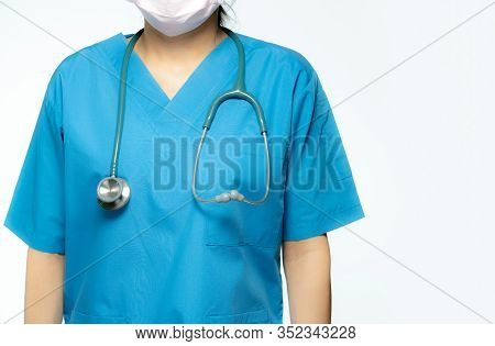 Asian Doctor With Stethoscope And Blue Scrubs Uniform. Doctor Wear Face Mask For Protect Wuhan Coron