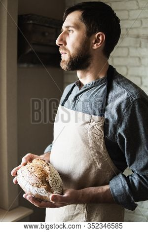 Bearded Young Man In Rustic Apron Holding A Loaf Of Bread In His Hands