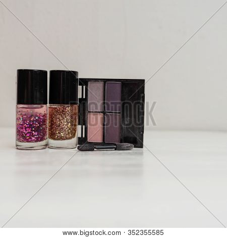 Cosmetics Isolated On White With Copy Space, Colorful Glittery Nail Polish With Eyeshadow Palette An