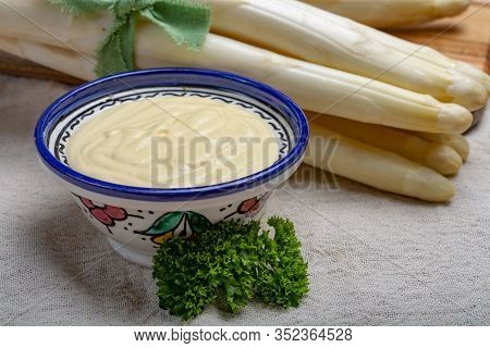 Bunch Of Fresh Uncooked White Asparagus And Hollandaise Sauce In Bowl, Tasty Vegetarian Food