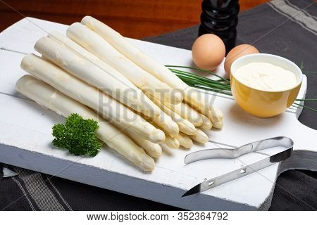Bunch Of Fresh Uncooked White Asparagus, Boiled Eggs And Hollandaise Sauce In Bowl, Tasty Vegetarian