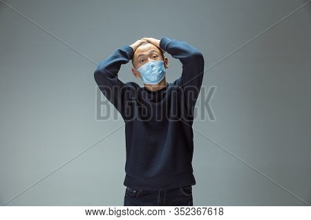 Sad, Upset. Chinese Man In Blue Protective Mask Posing. Prevention Against Pneumonia Respiratory Sym