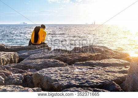 Back View Of A Man In Yellow Shirt Sitting On A Rock By The Sea. Leisure Time And Relaxing  Concept.