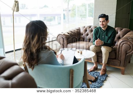 Businessman Listening To Female Counselor During Therapy Session While Sitting In Office