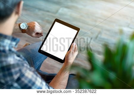 Man hold tablet computer with isolated screen in his hand, and looking what time o'clock. Clipping path.