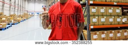 Logistics Warehouse Keeper In Red T-shirt Against Goods Close-up.