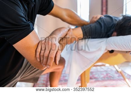 Professional Massage Therapist Working On A Man Hand. Sports Injury Rehabilitation Process. Therapeu