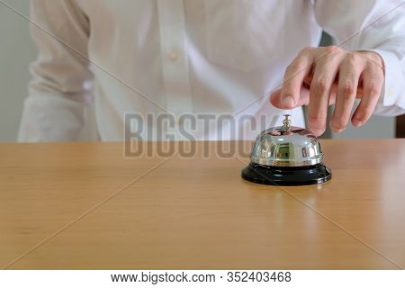 Men Wearing White Shirt Reaching His Hand And Finger To Ring A Reception Or Restuarant Bell On Wood