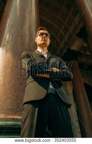 A portrait of a goodlooking young student posing in the street. Men's beauty, fashion.