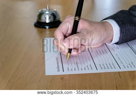 Men Business Person Use Pen To Writing On A Hotel Reservation Form At Reception Concierge Desk. With