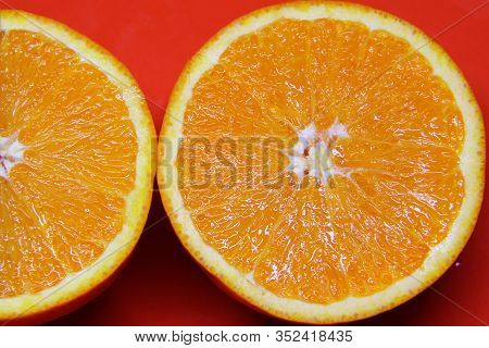 Two Half An Orange On A Red Background, Juicy Orange Fruit. Concept Of Healthy Food, Proper Nutritio