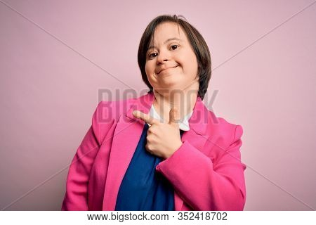 Young down syndrome business woman over pink background cheerful with a smile of face pointing with hand and finger up to the side with happy and natural expression on face