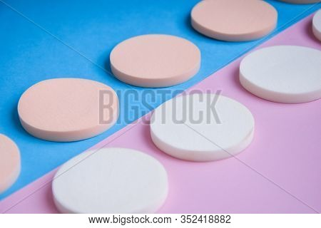 White And Beige Makeup Sponges On The Blue And Pink Background, Close Up, Cosmetic Sponges Powder Fo
