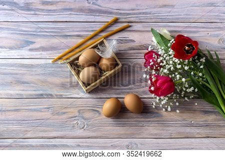 The Easter Composition. Eggs, A Red Tulips And Church Candles On Wooden Table Close-up.