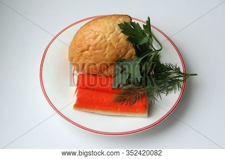 Still Life Of A Piece Of White Bread, Crab Sticks And Parsley On A White Plate With A Red Border. St