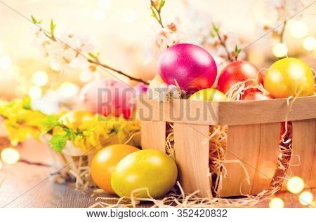 Easter colorful eggs in the basket. Beautiful colourful yellow, pink and orange color eggs with decorations and spring blossoming flowers over bright blurred bokeh, spring holidays background