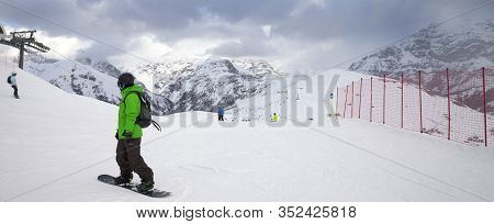 Snowy Ski Slope With Snowboarders And Skiers In High Mountains And Cloudy Sunlit Sky At Winter Gray