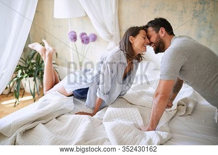 couple cuddling  in the morning while making the bed. bedroom, morning,  togetherness, concept