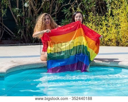 Stock Photo Of Two Girls From Different Ethnic Groups Sitting At The Edge Of A Swimming Pool Showing