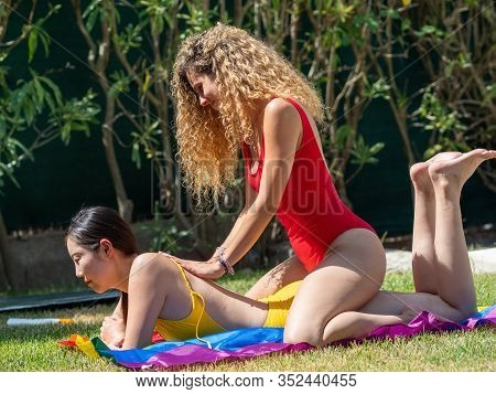 Stock Photo Of An Asian Girl Stretched Out On The Lawn Over An Lgtb Flag Waiting For A Blonde Girl T